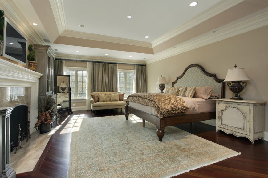 A Spacious Bedroom With Hardwood Floors And A Stately Fireplace. Two Large  Windows Are Inset
