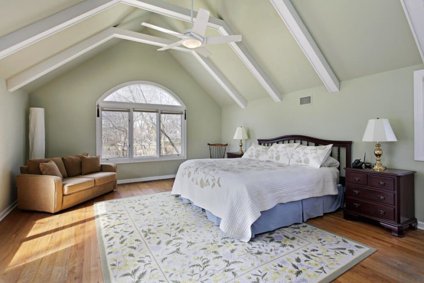 A Simple, Charming Attic Bedroom With Exposed Rafters Painted White And A  Single Loveseat In