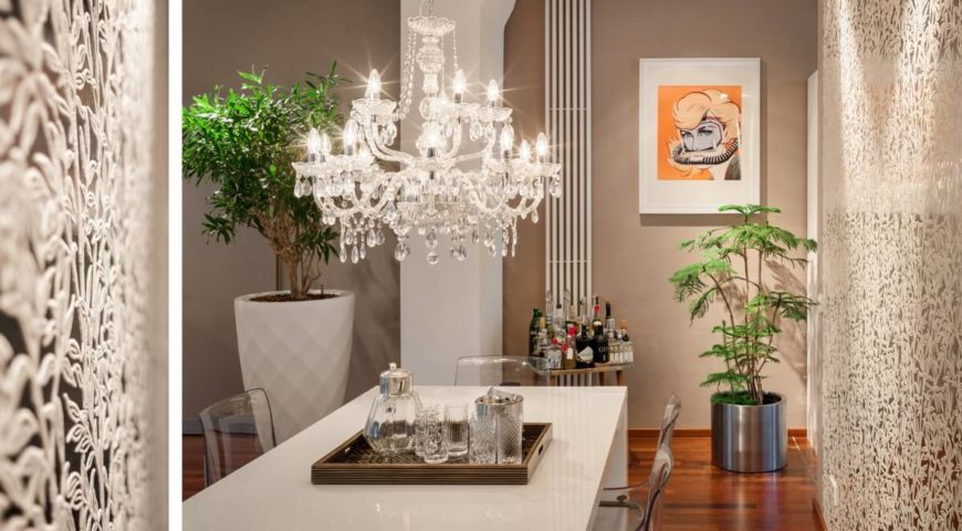 From the dining table itself, you notice the modern styling of the see-through ghost chairs. Looking closer at the metalwork of the wall, you begin to notice the intimate details in the design, possessing a floral theme, which is perpetuated by the potted plants against the far wall.