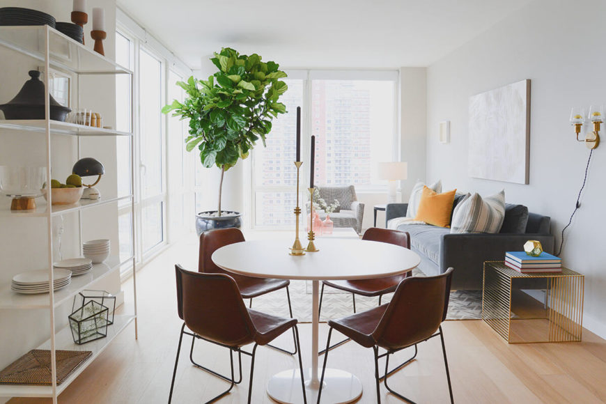 The home centers on an open plan space including this dining area and  family room. Striking Modern Design in Midtown by Homepolish