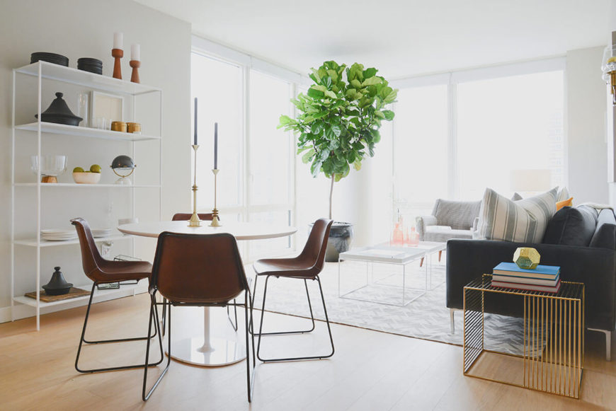 The family room stands awash in natural light, courtesy of full height windows covering two walls and an open design that diffuses sunlight throughout. The white space is shot through with subtle color, centered on a large tree planted in a corner container.