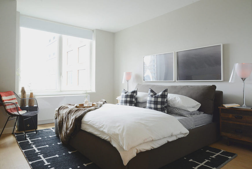 The master bedroom, also wrapped in white with light hardwood flooring, centers on a large leather upholstered bed in grey. A black and white patterned area rug fills the middle of the space, while rustic styled bedside dressers provide utility and storage.