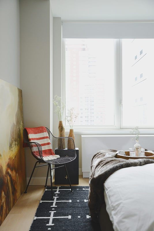 Next to the immense windows, this black metal mesh accent chair holds a corner. A large landscape painting adorns the left wall, adding complexity and contrast to the bright room.