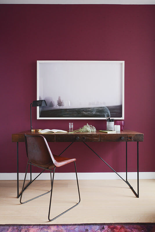 The simple and elegant desk makes for a perfect foil to the sumptuous wall and area rug coloring.