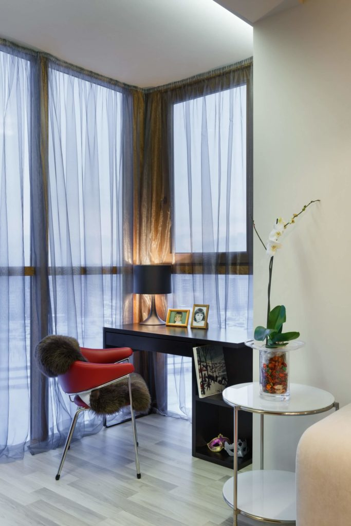 Near the beautiful floor to ceiling windows covered in