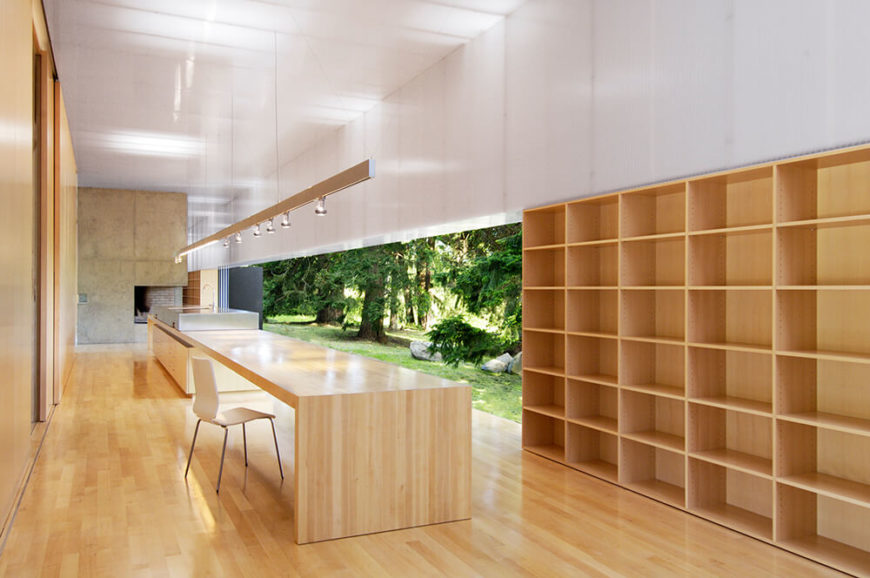 Now we move inside the home, witnessing the subtle glow of the acrylic wall panels and the interplay between sleek modern structures and rich natural wood materials. The kitchen centers on this massive island, boasting a sink, cooktop, and extensive dining space.