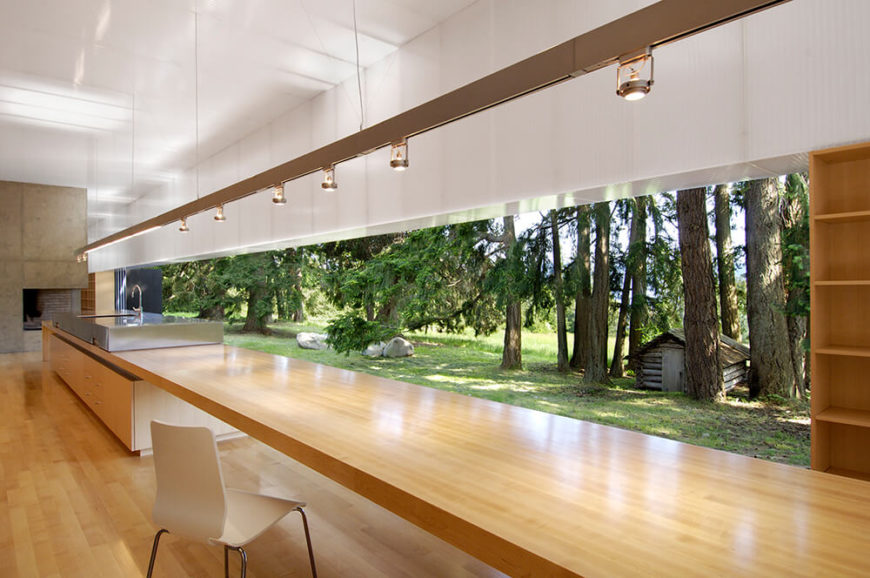 The sleek natural wood helps the ultra-modern interior blend with its natural surroundings, offering a warm touch to the minimalist structure. A slim line of lights are wire-hung down the length of the room.