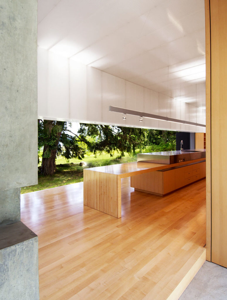 The acrylic wall panels surrounding this space positively glow in contrast to the neutral concrete and warm natural wood tones.