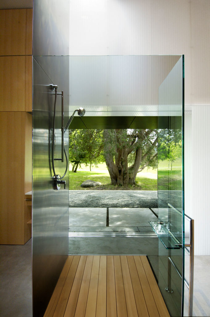 Here's a bathroom within the home, showcasing the innovative layering of the structure at its most complex. The interplay between steel, natural wood, concrete, and glass can be opened so that even a shower feels like it's taking place outdoors.