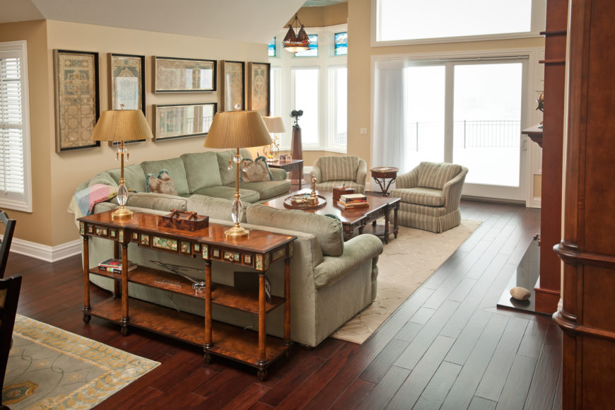 The living room centers on a large L-shaped sectional in light emerald tones paired with an armchair duo and large rich wood coffee table over a beige area rug. Deep, rich hardwood flooring fills the entire open-plan central space of the home, connecting the kitchen, through to the living room.