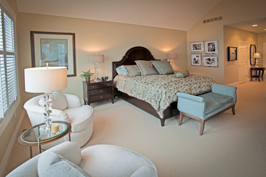 The master bedroom sports a beige and white palette, spiked by the appearance of light blue in the form of a bench seat and accent pillows on the bed. The rich wood bed frame is flanked by matching bedside dressers, while a pair of white club chairs flank a glass topped table beneath windows at left.
