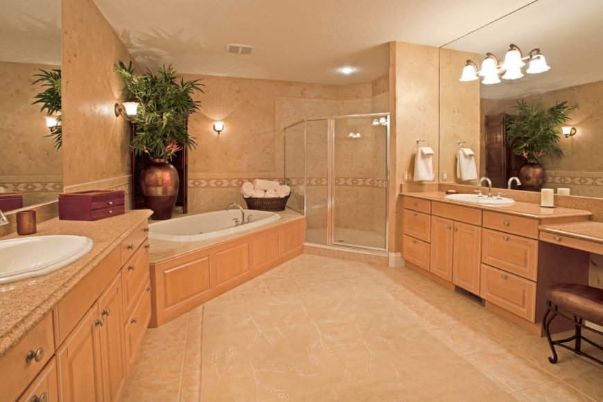 The master bath is awash in light natural wood cabinetry and beige tile flooring and bath surround. The large space holds enough room for two full vanities with massive mirrors, while the soaking tub fills a corner next to the glass enclosed shower.