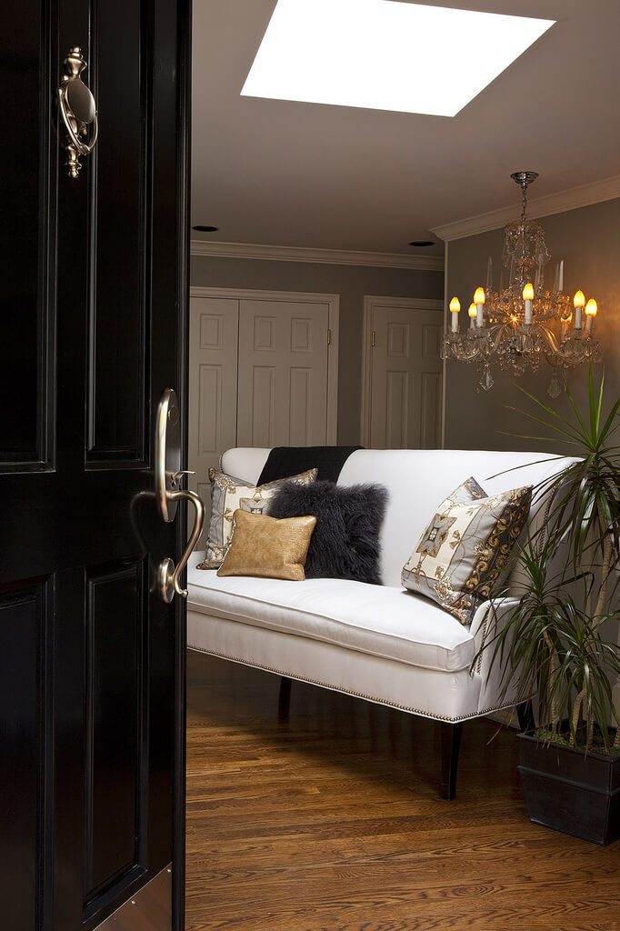 Opening into this warm toned foyer, we see a pristine white, nailhead trim sofa standing over the hardwood floor beneath a chandelier and large skylight opening. The jet black front door adds contrast and elegance.