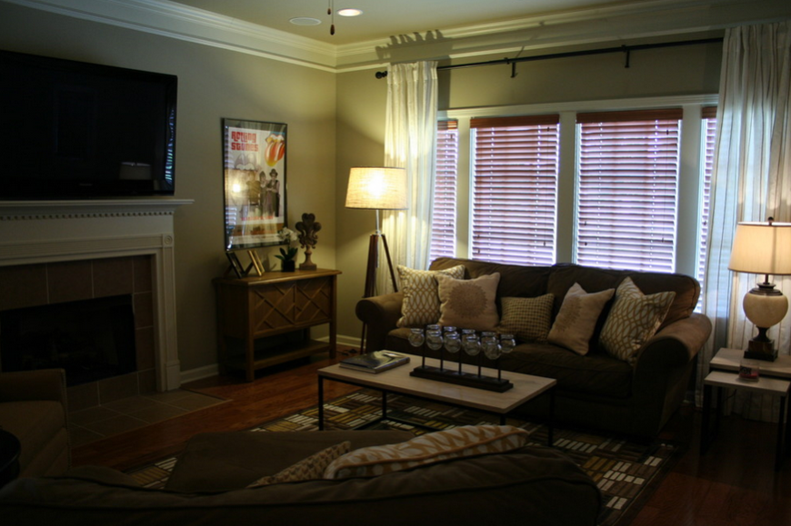 The living room, centered on a large fireplace with television mounted above the white mantle, features a high texture area rug over hardwood flooring. Mocha brown sofas are countered with high texture throw pillows, while light hued walls make the space inviting.
