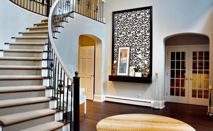 The grand foyer is overlooked by a catwalk-style upper hall, with curved staircase leading down to dark hardwood flooring. The bright walls allow details like the painted art shelf to really stand out.