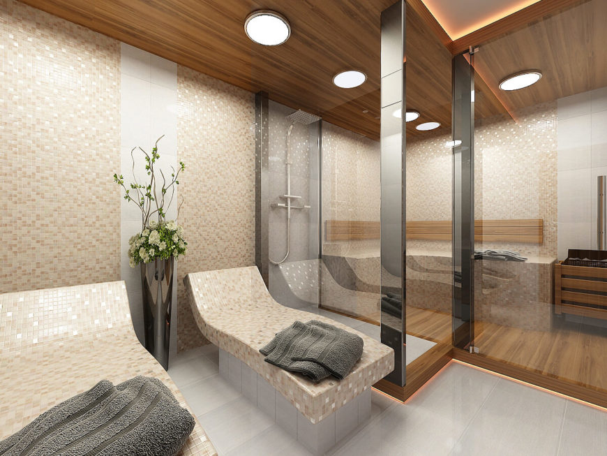 The in-house spa room features a steam room, shower, and tiled lounges. The peach tones in the tile complement the wood accents and the warm under lighting that runs along raised floor and the recessed ceiling.