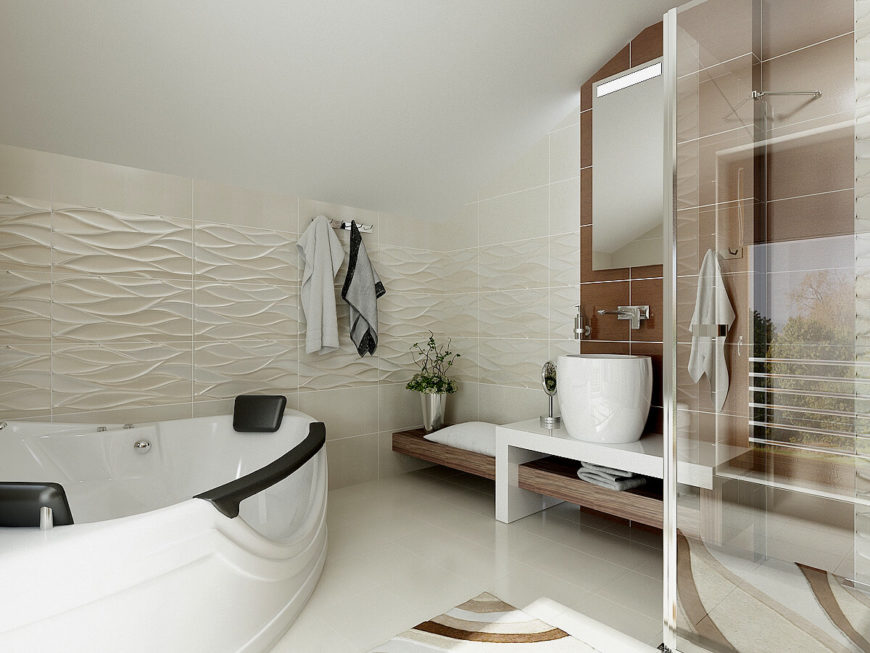 The master bathroom continues the white theme with similar wood accents. The textured tiling on the wall is reminiscent flowing water. This bath features a large tub, walk-in shower, and cool white tiles.