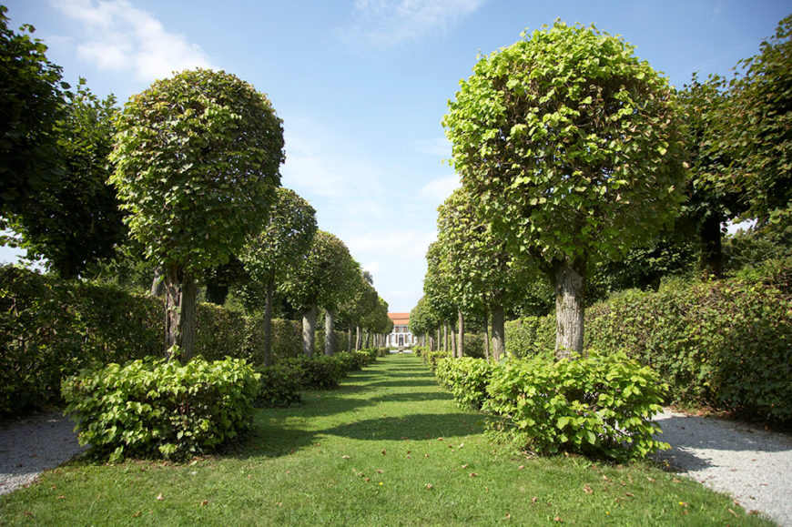 The combination of hedges and the lines of manicured trees make a regal entrance path that leads up to the beautiful house in the background. Partnering squared hedges with the rounded trees creates a lovely balance in shapes when using similar materials.