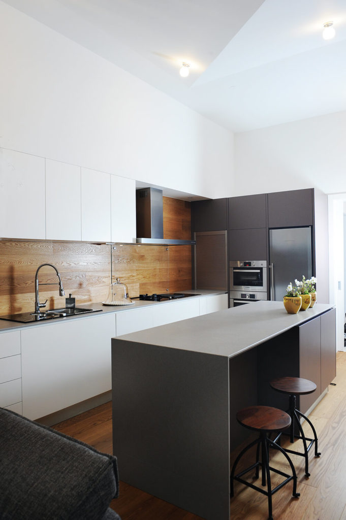 The kitchen is flush with sleek, hardware-free cabinetry in white, contrasting with the natural wood panel backsplash that matches the flooring. Stainless steel appliances and the sharp, modern style informs the contemporary look.