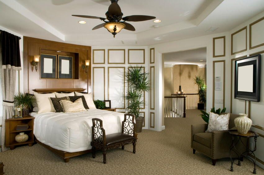 This interesting small bedroom is light and welcoming, with incredible attention to detail.  The darker furniture blends in with the variety of patterns and mouldings commanding your attention.  A striking beige-gold pattern carpet is mimicked in the gentle tendrils of the leather, wood, and metal settee, and is coordinated beautifully in the moulding details on the wall.