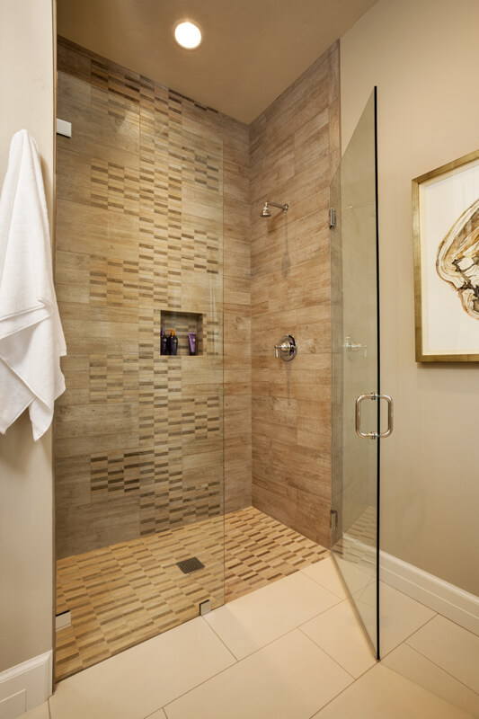 beige tile gives way to intricate tile patterns within the shower