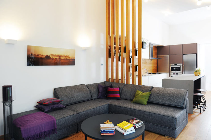 Moving into the living room space, we see a large contemporary grey L-shaped sectional hugging a matching circular coffee table. The bright walls act in contrast to the deep toned furniture.
