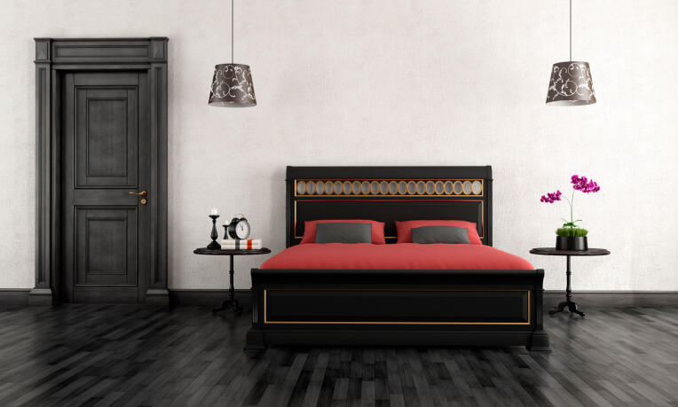 The glossy black hardwood flooring of this room is unusual and eye catching beyond compare.  Were it not for the vivid white wall for contrast coupled with the bold crimson linens on the bed,  the ebony bed frame, door, and night stand details might otherwise be somber.  Instead, we have a striking and cohesive bedroom perfect for a good night's sleep.