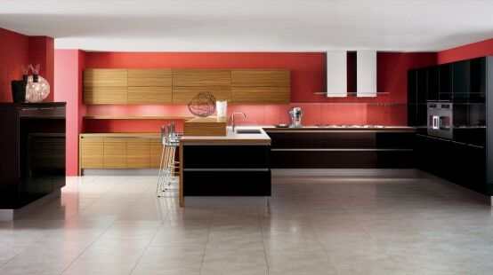 The reds in this room are a background color to the gorgeous light natural hardwood. The black U-Shaped countertops create a bold contrast with the natural wood and grey tiled flooring.