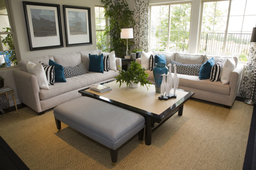This gray, tan, and cream room is highlighted by teal accent pillows and accessories. Greenery is provided by several houseplants, and a natural fiber area rug brings us that much closer to the great outdoors. Pops of white can also be seen, and interestingly patterned draperies and throw pillows create a dynamic space.