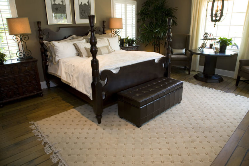 This impressive master bedroom features an extremely deep brown four post bed, leather chest bench, and coordinating end tables. The ornate metal lamps with light shades offer a soft ambiance, while a natural hardwood floor is dressed up with a large, light area rug.  This thoughtfully designed space ensures that window space allows sunlight to flood through the room from multiple angles.