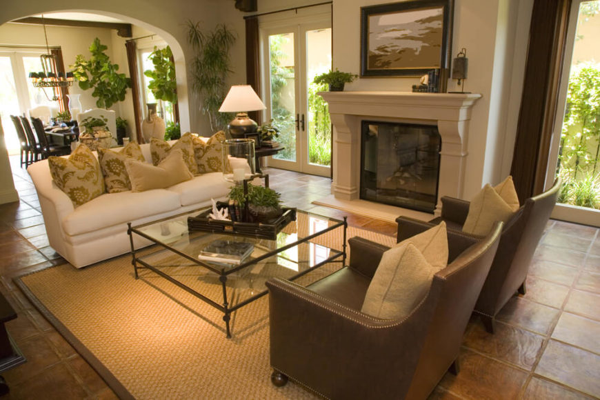 This small living area is awash in earth tones, and surrounded by windows looking into a garden area.
