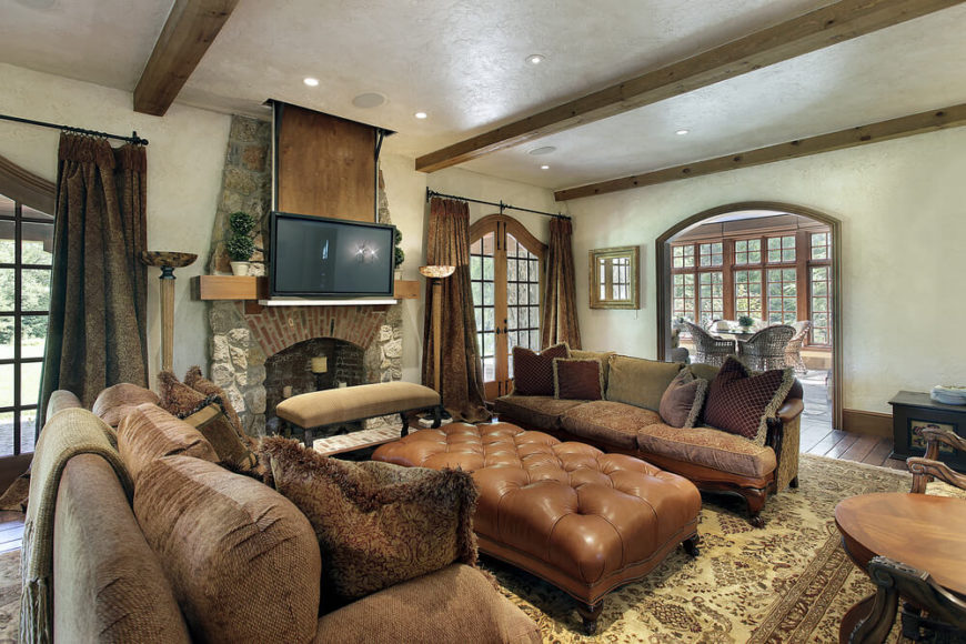 This masculine living space incorporates earth tones to their full potential. A plush, overstuffed, light brown ottoman acts as a resting place for weary feet for guests of two sofas. A large traditional area rug sits atop a dark hardwood planked floor, adding warmth to this rich space. A stone fireplace makes the space cozy, while numerous delicately designed windows brighten the space with outdoor light.