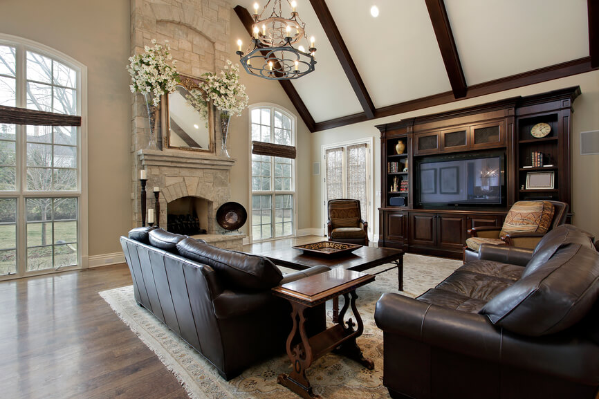 A luxurious traditional living room space incorporates deep brown, beige and ivory to achieve a look rich in luxury and comfort. A sizable area rug sits atop a hardwood floor, while a grand entertainment center faces the leather sofas. Tall arched windows give a peek into the outdoors, and a fireplace waits to bring cozy warmth to the entire area.