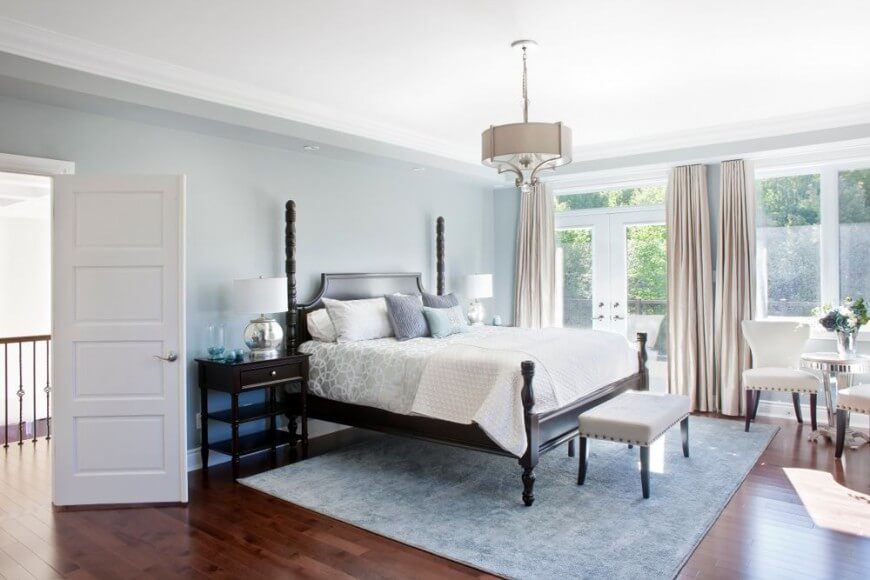 This bright and cheery bedroom demonstrates that dark furniture does not mean a dark space!  Crystal clear floor to ceiling windows, light upholstery and soft baby blue and gray tones work together to ensure a crisp, clean room.  The exquisitely dark furniture offers a high contrast to the snow white details and the ample sunlight pouring in through the french doors.  A view of the patio and outdoors brings one closer to nature, and is perfect for slowly drifting off to sleep.