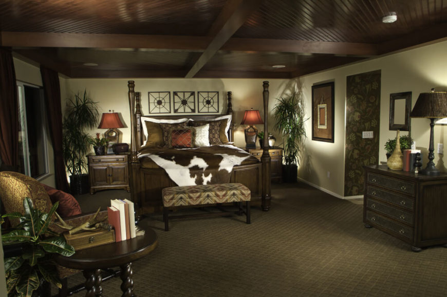 This room is richly decorated and features a variety of earth tones, patterns, and textures. While dark furniture with a dark ceiling was a bold design risk, the beige walls, patterned carpeting, and splashes of bright white of the cowhide throw and pillows allow your eye to be drawn in and around the room to appreciate the design details and allow for luxurious relaxation.