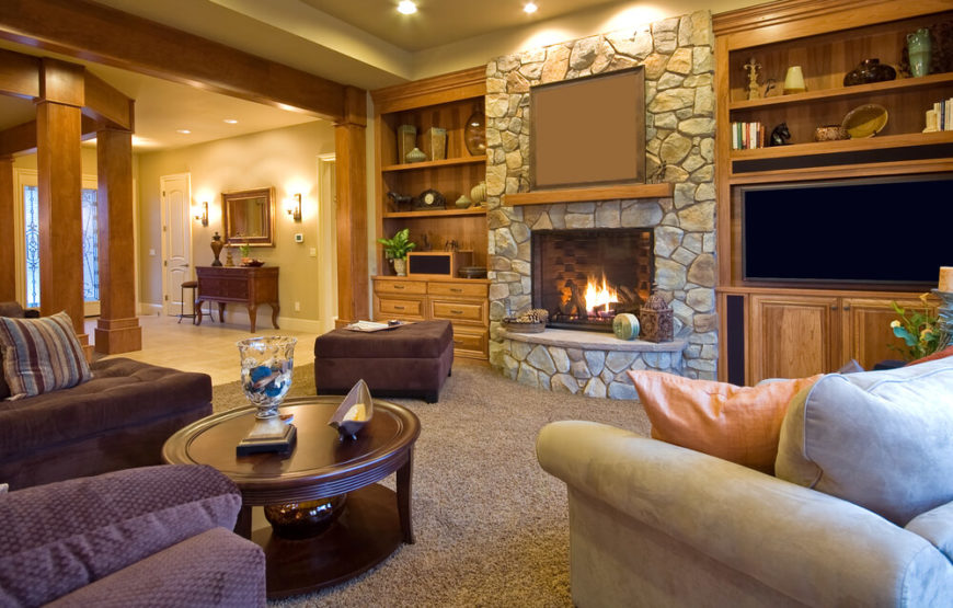 This cozy living room area is as functional as it is gorgeous. A large stone hearth takes center stage, while grays, browns, and plums complement each other. Two flat screen TVs allow for optimal viewing at multiple angles in the room, and a view of the entryway can be seen where guests can be quickly ushered into this comfortable space.