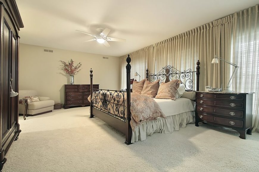This bedroom is another great example of using light colors and utilizing the stark contrast between the furniture and surroundings to great effect.  The carpeting, walls, lounging chair, and lighter linens almost blend together.  A darker patterned duvet cover and throw pillows complement the various shades of light beige throughout.  A four post bed with an ornate metal headboard and footboard work beautifully with the antique look of the rest of the bedroom furniture.  Modern table lamps seem almost out of place, yet somehow work perfectly with this simple yet opulent bedroom.