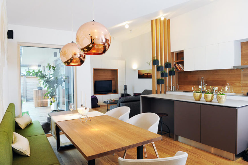 This modern home features rich natural wood and bright walls throughout its open-plan design.