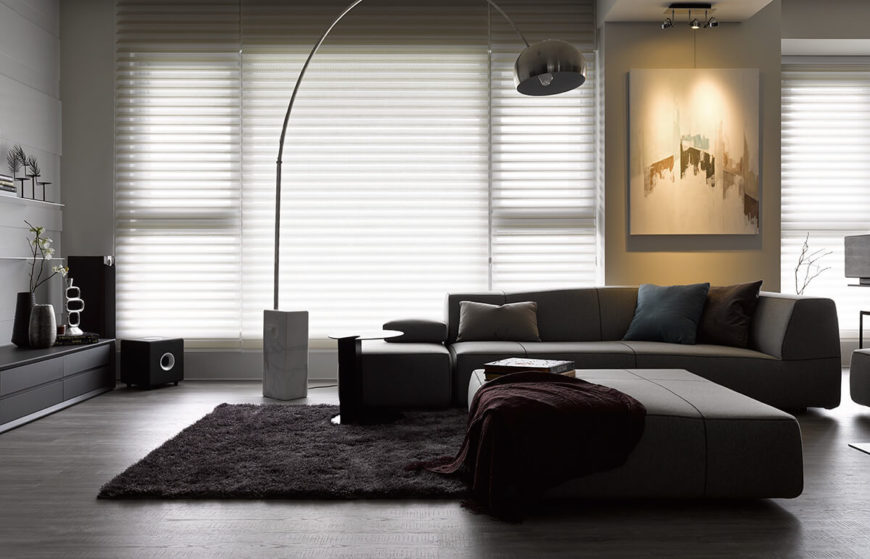 The dark contemporary sectional and black shag rug in this room keep an elegant tone, lightened via sunlight through the full height window sets. The sparse, minimalist layout expands the visual space.