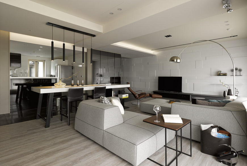 The sectional can be reconfigured to change the layout of this room. At center, the island functions as a dining space, storage, and room divider.