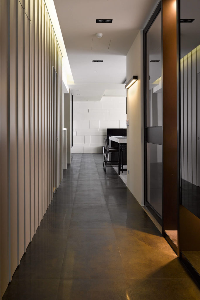 A long view down the hallway reveals the striped wall texture at left and glass panels at left, partially obscuring the room beyond.