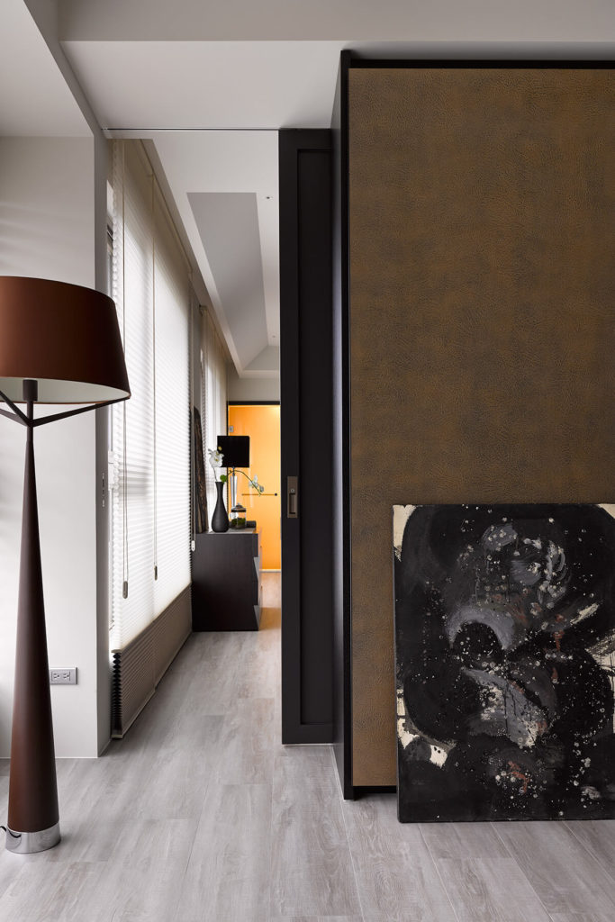 Here we see a dark stained wood pocket door, emerging from the wall to help separate the rooms when privacy is needed.