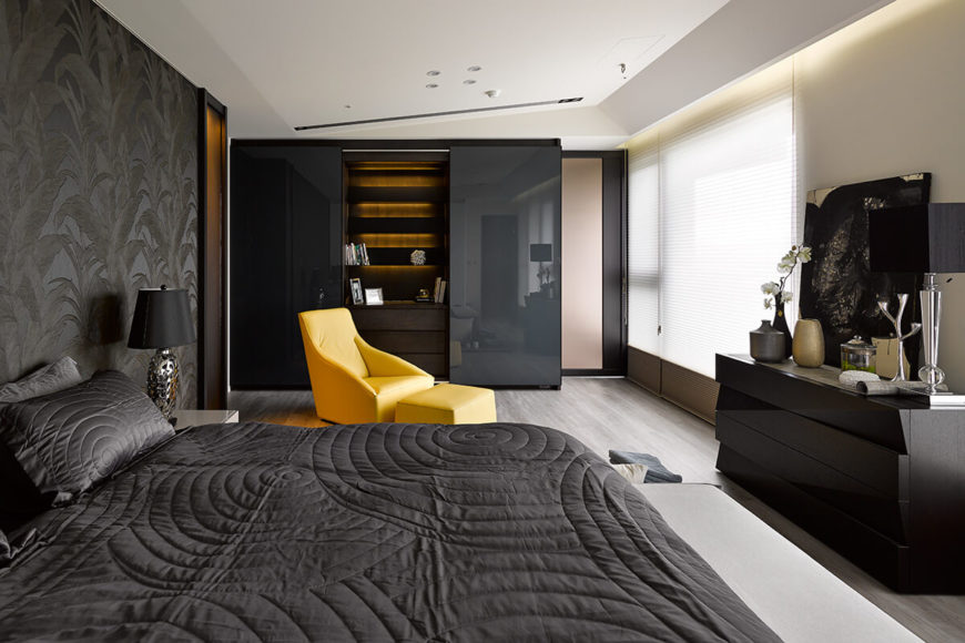 The closet features a truly innovative concealment, with glossy outer sliding panels revealing a dresser and inner-lit shelving within. A jet-black dresser at right features similarly glossy drawer surfaces.