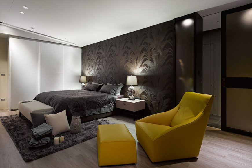 The bed itself is flanked by a pair of glossy white dresser tables, with a contemporary grey bench at the foot. The bold yellow chair and ottoman are leather upholstered in a minimalist contemporary style.