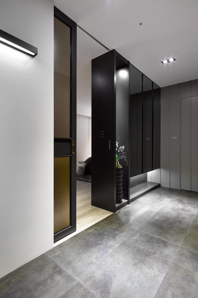 The entrance to the master bedroom sports another pocket door, and is framed by a glossy black wall with inner-lit display shelving.