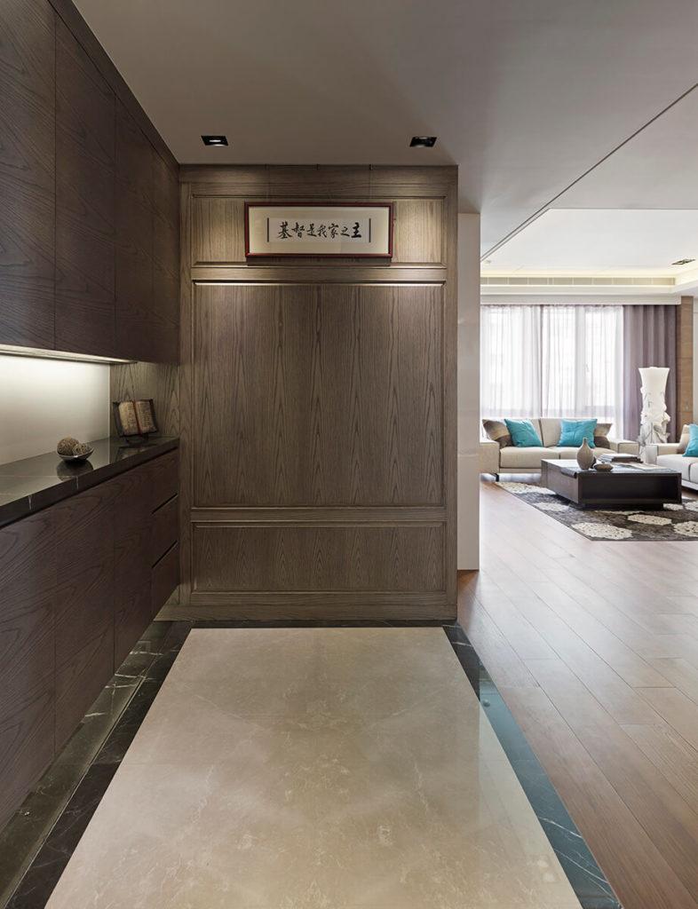 In the entryway, a slim marble floor segment highlights the bespoke arrangement of dark wood and sleek paneling.