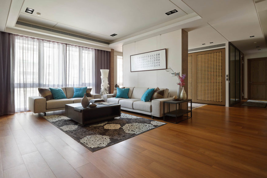 The rich hardwood flooring expands throughout the open-plan space, connecting the various neutral-toned areas within the home. Contemporary furniture combines with traditional artwork for a timeless style.