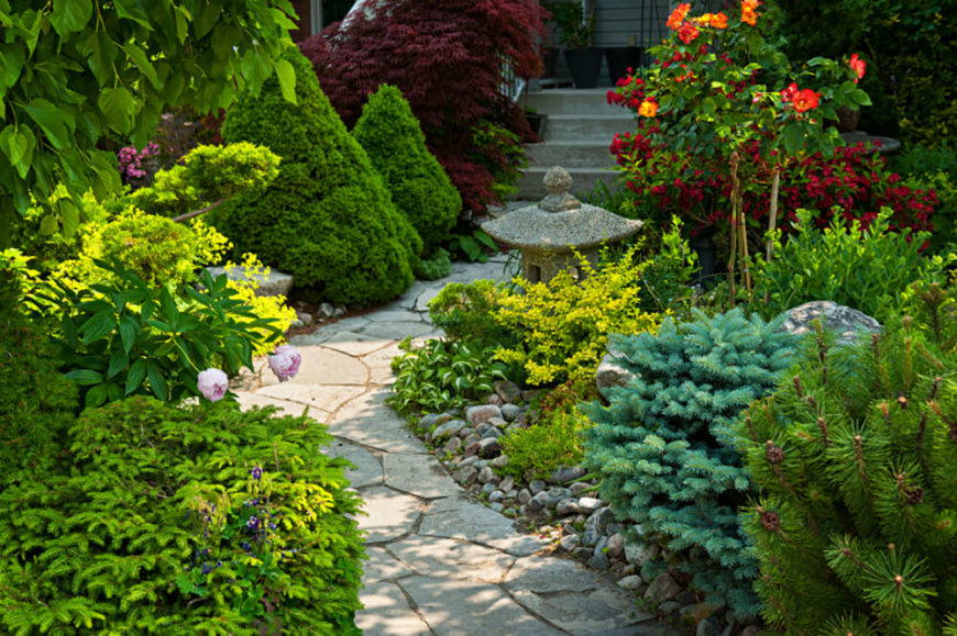 This Calming Garden Features Small Shrubbery And A Japanese Lantern Along  The Pieced Together Pathway