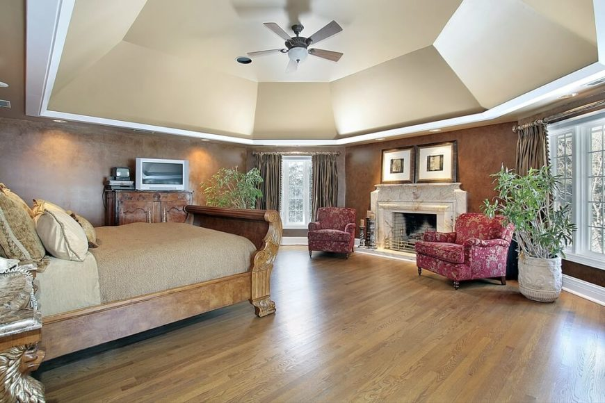 The soaring ceiling is a real standout in the above design. It floats proudly above honey hardwood floors, a wonderful sleigh style bed bedecked in beige neutral linens, magenta and beige patterned accent chairs, and a beautiful fireplace.  The walls are textured in such as way as to be reminiscent of the woodwork on the bed.  A flat screen TV is perched atop a coordinating stand and is visible from both the bed and accent chairs.