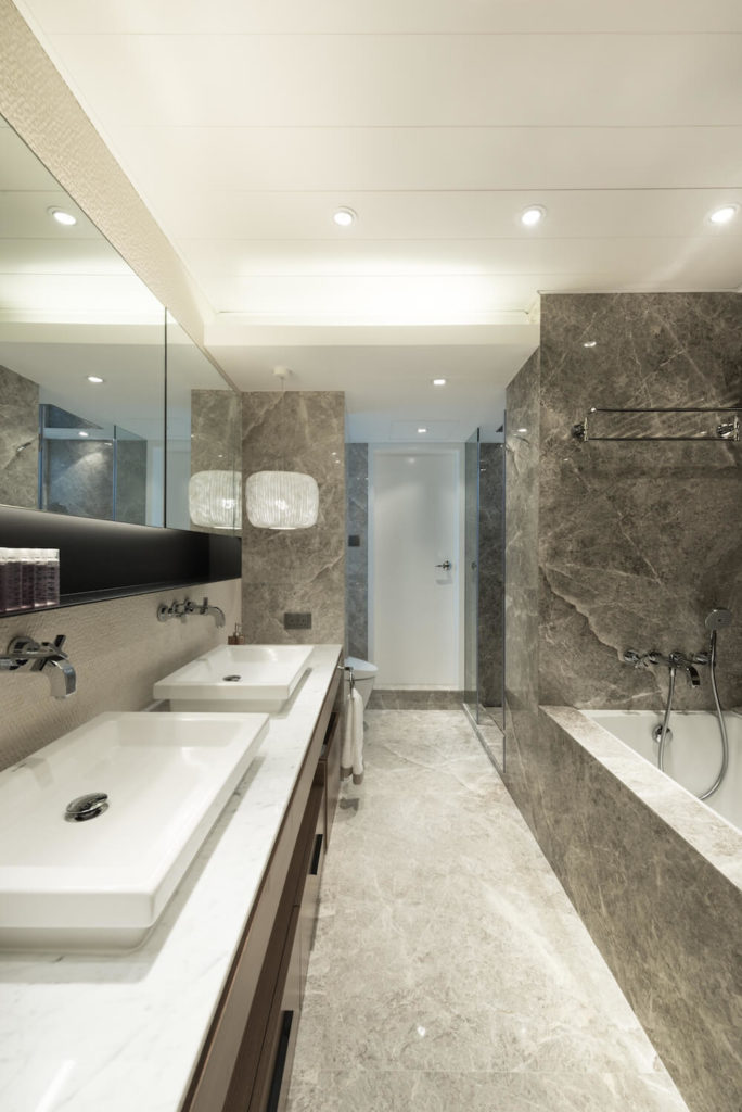 The bathroom is almost completely marble. The entire space is very open and polished, with a pair of vessel sinks on the lengthy vanity.